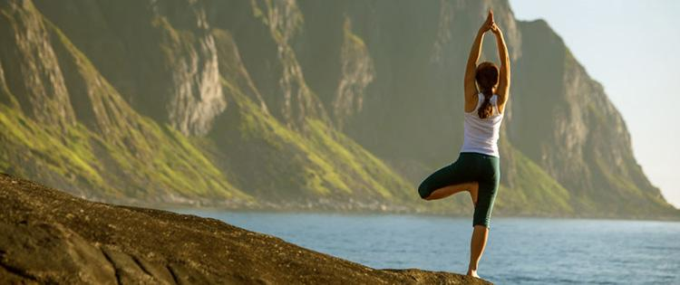 Back of woman standing on one leg in yoga pose in front of a body of water