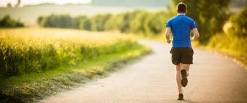 photo of man running along path on a sunny day