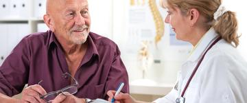 Doctor discussing information with elderly, male patient