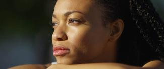 Photo of a young Black woman thinking and looking toward sunlight