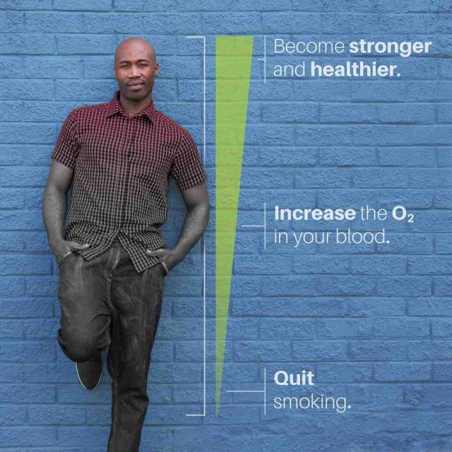 "Man standing against wall next to line depicting increase in oxygen and strength after quitting smoking with text at the bottom saying ""quit smoking"", text in the middle saying ""increase the O2 in your blood"" and text at the top saying ""become stronger and healthier"""